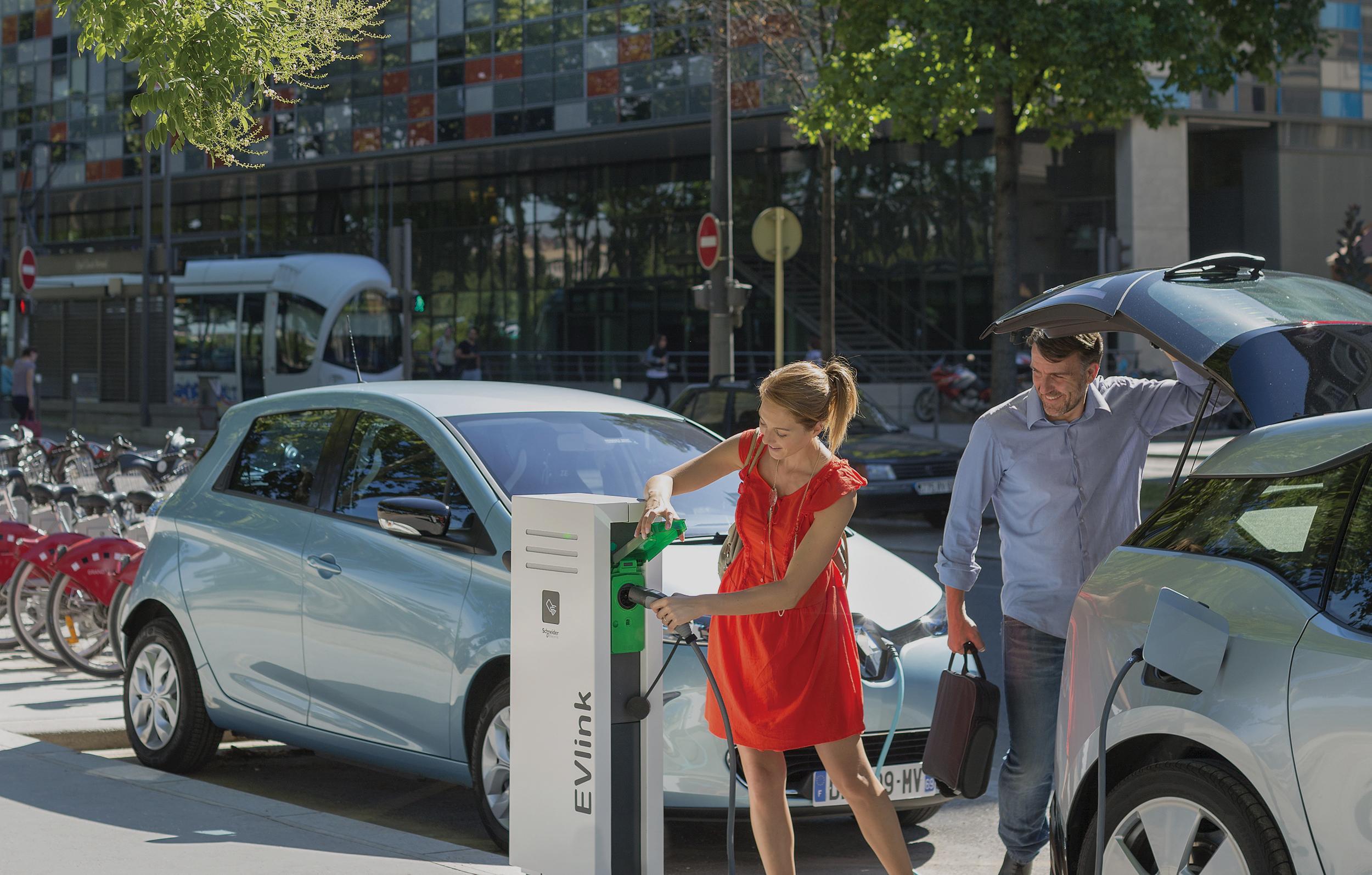 Couple voiture électrique borne recharge